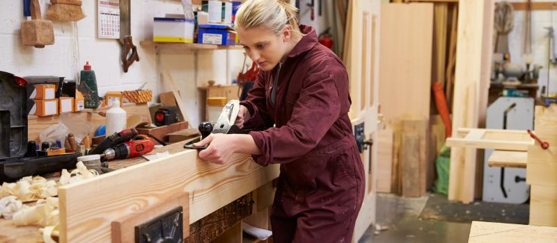 bigstock Female Apprentice Planing Wood 87401303